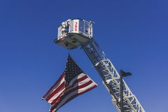 An American Flag is Hoisted Up by a Fire Truck in Remembrance on September 11th, 2018 stock images