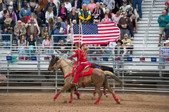 American flag on horseback. APACHE JUNCTION, AZ - FEBRUARY 27: Two girls on horseback display the American flag at the Lost Dutchman Days rodeo on February 27 stock image