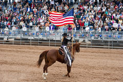 American flag on horseback. APACHE JUNCTION, AZ - FEBRUARY 27: A rodeo queen on horseback displays the American flag at the Lost Dutchman Days rodeo on February royalty free stock photo