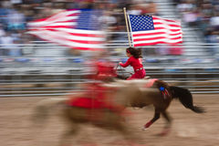 American flag on horseback. APACHE JUNCTION, AZ - FEBRUARY 26: Two girls on horseback display the American flag at the Lost Dutchman Days rodeo on February 26 royalty free stock photography