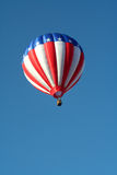 American flag hot air balloon. Low angle view of hot air balloon with American flag in flight; blue sky background Stock Photos