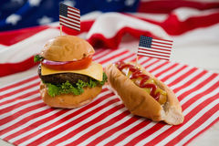 American flag with hot dog and burger on wooden table Royalty Free Stock Photography