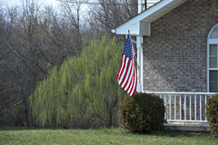 American flag on house porch. American flag flying from porch of home with weeping willow tree in background, U.S.A royalty free stock photography