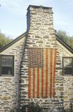 American Flag Hung on Stone Chimney of House, New England Royalty Free Stock Images