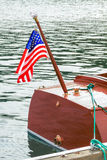 American flag flies behind classic wooden boat Royalty Free Stock Image