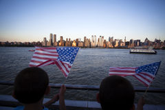 American flag during Independence Day on the Hudson River with a view at Manhattan - New York City - United States. Little children holding the American flag Stock Photo