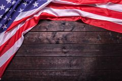 The American Flag Laying on a Wooden Background. The American Flag Laying on a Rich Old Wooden Background Royalty Free Stock Images