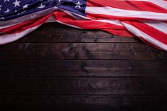 The American Flag Laying on a Wooden Background. The American Flag Laying on a Rich Old Wooden Background Royalty Free Stock Photo