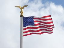 American flag in the light and the wind with a cloudy sky in the background stock photo