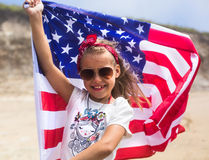 American Flag. Little smiling  patriotic girl with long blond hair, red head band  bandana and sunglasses holding an  waving in the wind on the ocean beach Royalty Free Stock Photography
