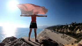 American flag Malibu. SLOW MOTION: Woman American flag in the blue sky from Point Dume promontory on Malibu coast in CA, United States above Point Dume Beach stock video