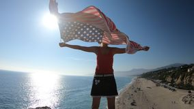 American flag Malibu. Woman holding an American flag looking Point Dume State Beach from Point Dume promontory on Malibu coast in CA, United States. Carefree stock video footage