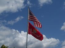 Two flags against a blue partly cloudy sky blow in the wind. The American flag and the Marine Corp flag fly in the breeze against a blue sky with white clouds stock photos