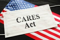 American flag and mask with sign cares act. Coronavirus Aid, Relief, and Economic Security law concept