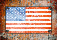 American flag on metal plate screwed screws on wall. Old grunge background Stock Illustration