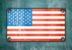 American flag on metal plate screwed screws on wall. Old grunge background Royalty Free Illustration