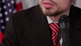 American flag, microphone and man. Guy speaking into microphone. Country needs a strong leader. Counselor's confident speech on TV stock video footage