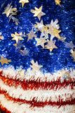 American Flag motif in red white and blue tinsel with sparkly stars with a bokeh blur effect - background or design element Royalty Free Stock Image