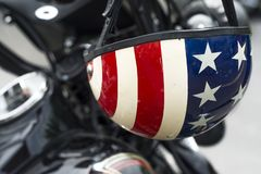 Closeup of red white and blue American flag motorcycle helmet. American flag motorcycle helmet hanging on motorcycle handlebars stock images