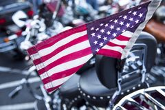 Close up of red white and blue with stars American flag on motorcycle. American flag on motorcycle with more motorcycles in background Stock Photography