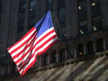 American Flag in New York City. Brightly lit American flag in New York City with dimly lit building as backdrop stock photography