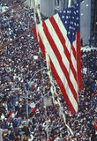 American Flag over tickertape parade. American flag flying over large crowd at tickertape parade, New York Stock Image