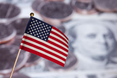 American flag over US banknotes and coins. Stock Photo