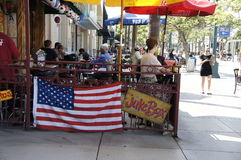 The American Flag, People, and Restaurants. The American Flag were displayed on the side bar fence in a restaurants to celebrate the 4th of July Independence Day Stock Photos