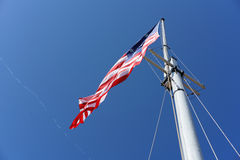 American Flag. Perspective from bottom up. Bright blue daylight sky Stock Photos