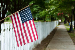 American flag on a picket fence. A small American flag adorns a worn, white picket fence in the summer Stock Photo