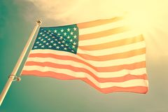 American flag on a pole floating in the wind, sun and blue sky. Vintage process Royalty Free Stock Photos