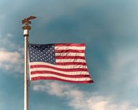 American flag waving in the wind against blue sky Stock Photos