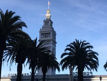 The glorious American flag proudly fly`s atop The San Francisco Ferry Building. The American flag, proudly flapping in the warmth and glow of another afternoon stock photo
