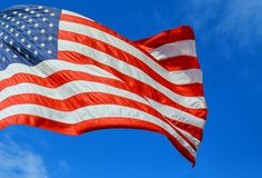 American flag red, white and blue with stars and strips in the wind blue sky. With clouds united states day usa independence national waving memorial patriotism stock photo