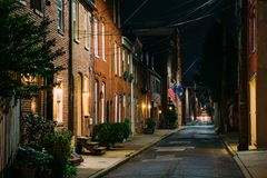 American flag and row houses on Bethel Street at night, in Fells Point, Baltimore, Maryland.  stock image