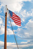 American Flag on a Sailboat Mast. With Clouds and Sky in the Background Royalty Free Stock Photo