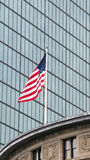 American flag and skyscraper. Exterior of modern skyscraper building with glass windows, American flag in foreground Royalty Free Stock Image