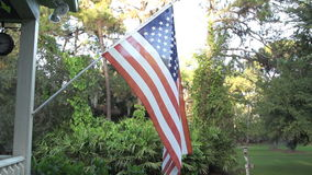 American Flag Slow Motion Tight. An American flag displayed on a front porch stock footage