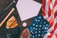 American flag and sport equipment with blank paper. On wooden table stock image