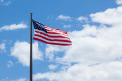 American flag - star and stripes floating over a cloudy blue sky Royalty Free Stock Image