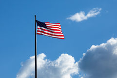 American flag - star and stripes floating over a cloudy blue sky Royalty Free Stock Images
