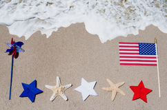 American flag with starfishes on the sandy beach Stock Photography