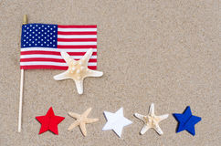American flag with starfishes on the sandy beach Stock Image