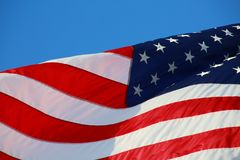 American Flag. The stars and stripes of the American flag wave and flutter patriotically in the afternoon sun Stock Image