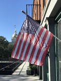 An American flag on a sunny day in front of the Savannah City Hall - GEORGIA. Savannah, a coastal Georgia city, is separated from South Carolina by the Savannah stock image