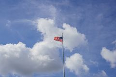 American flag swinging in a blue sky with clouds scene. At Los Angeles, California stock photography