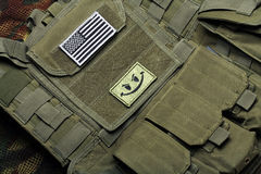 American flag on tactical vest. American flag with smile sign on a green tactical vest. Close-up Royalty Free Stock Photo