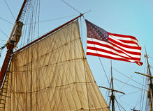 American Flag With Tall Ship Sails, California. United States of America flag waves in the wind, attached to the sails of a tall ship at the San Diego royalty free stock photo