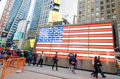 American flag at Times Square in New York City. Tourists walk past the electronically lit American Flag that dominates the scene in Times Square Stock Image