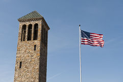 American flag and tower in the sky. American flag flying in a blue sky by the Luray Singing Tower in Luray, Virginia Royalty Free Stock Image